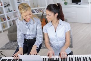 adult woman learning piano from her teacher