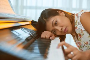 woman looking bored leaning on her piano
