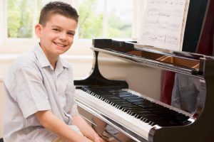 smiling child about to practice his piano