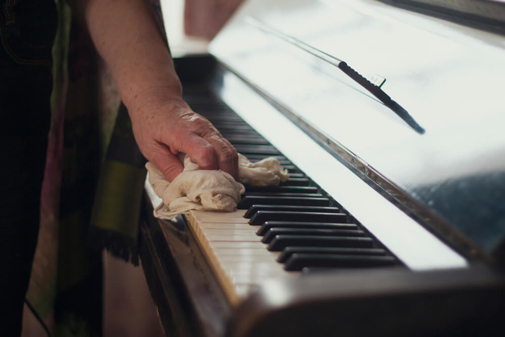 female hand cleaning piano keys with a soft cloth