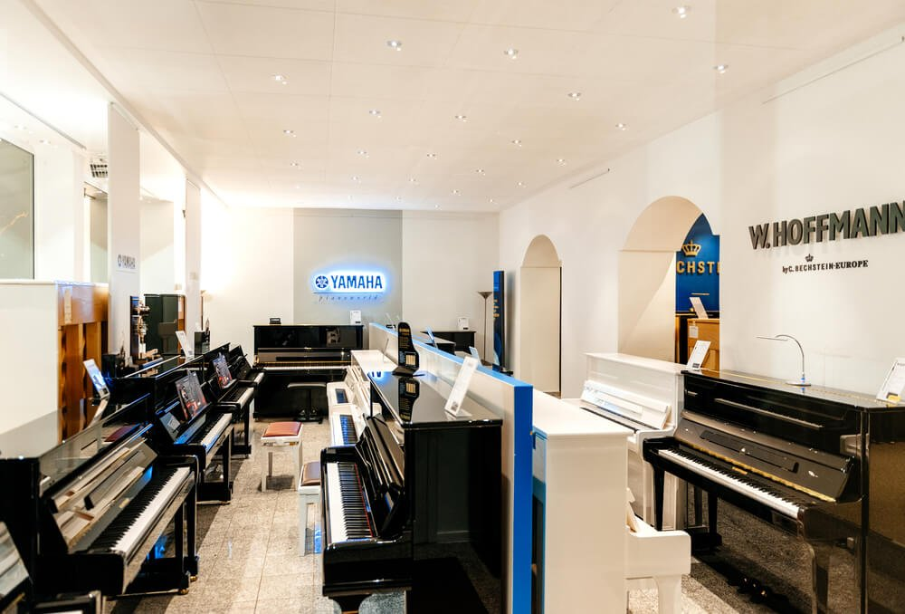 different kinds of pianos lined up in a music store