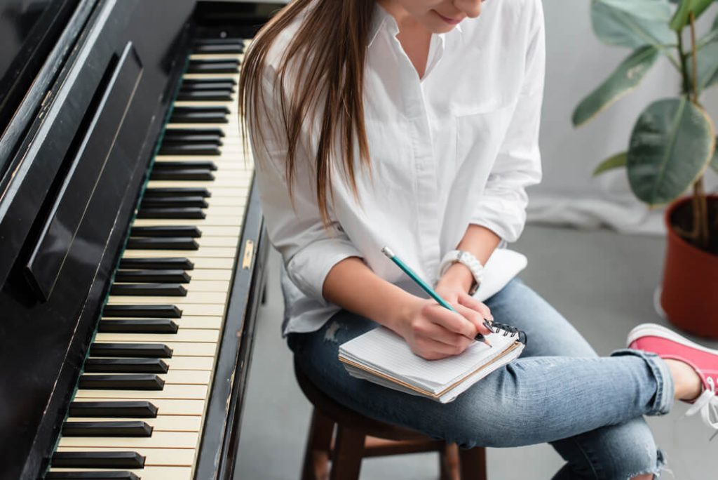 girl siting on a kitchen stool next to the piano