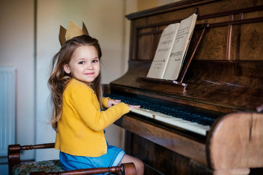 little girl in dress playing old wooden piano