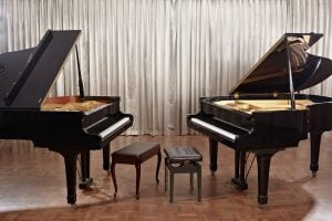 grand piano and baby grand piano on a stage
