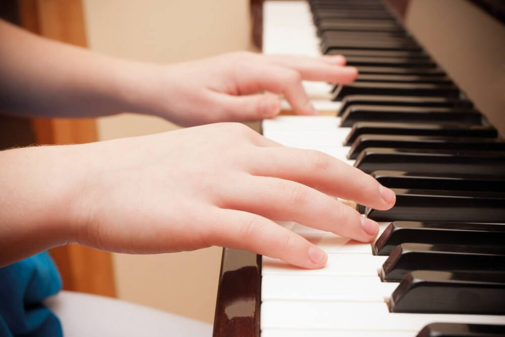 close up of the hands of a child playing piano