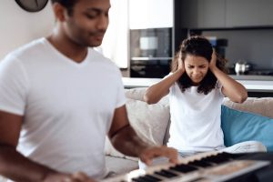 man playing piano and girlfriend covering ears