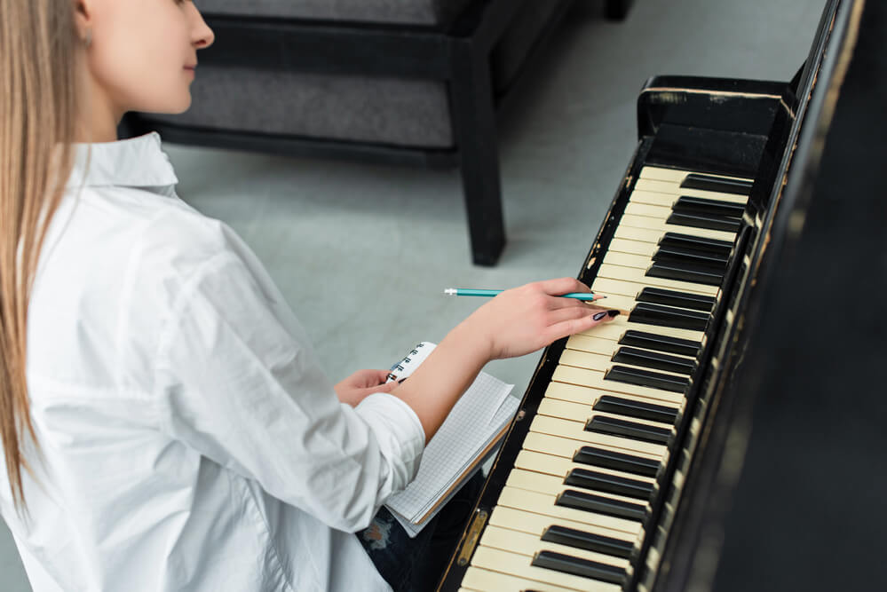 woman sitting at a piano and writing in a notebook