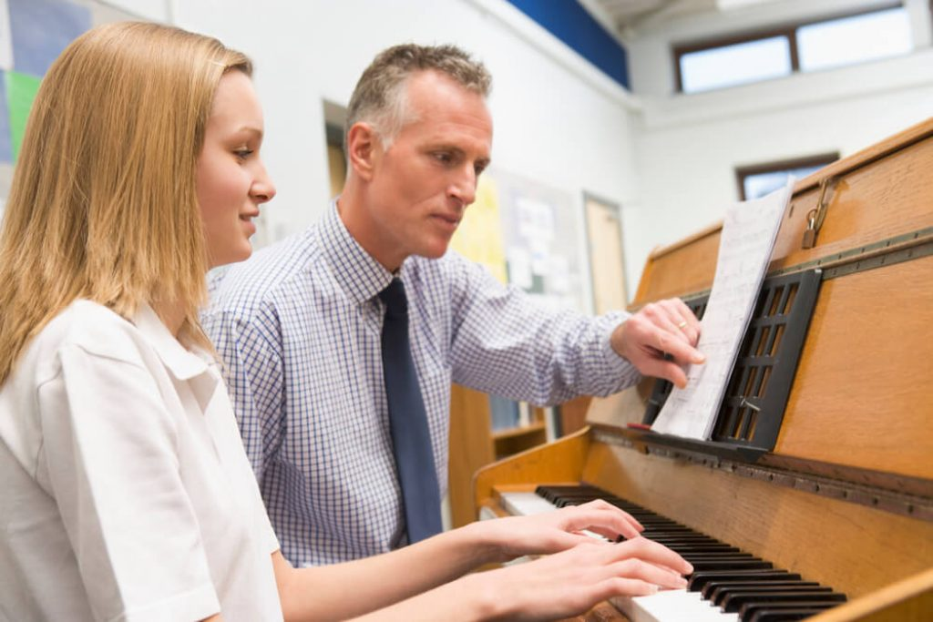 teen piano student being taught by her piano teacher