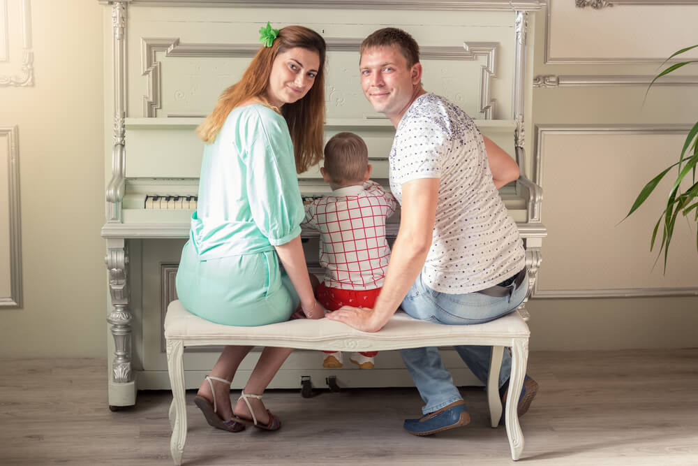 family sitting together on a piano bench