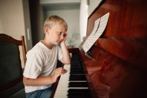 child with bored face pecking at a piano
