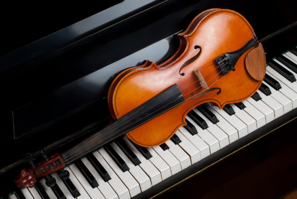 violin laying on a piano keyboard