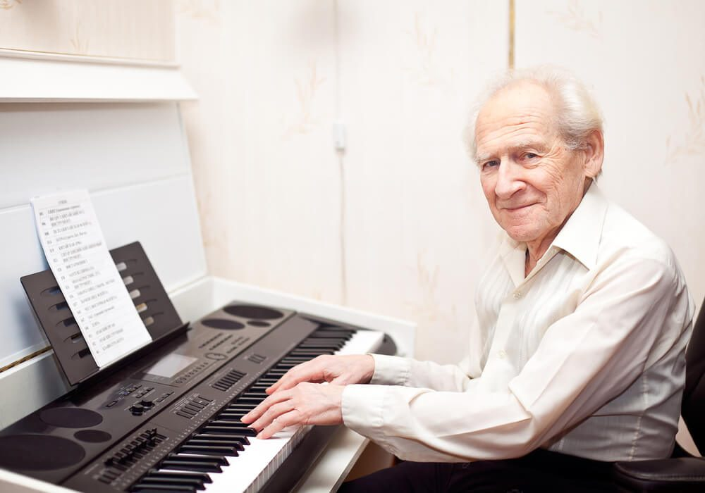 elderly man playing an electric keyboard