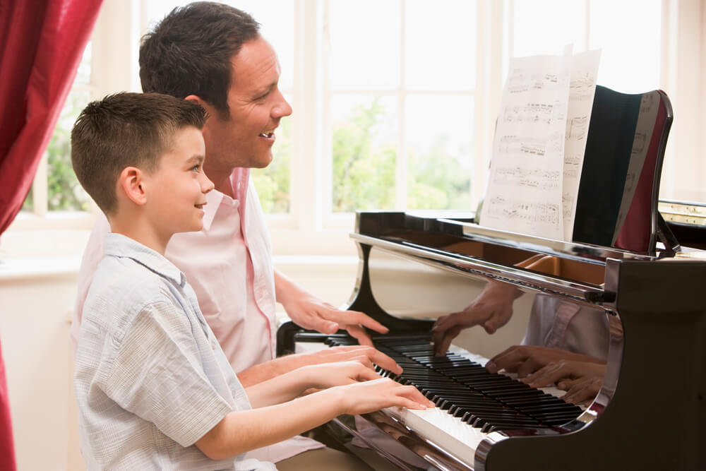 man and boy playing piano together