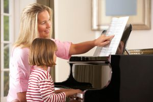 mom helping her daughter learn to play the piano