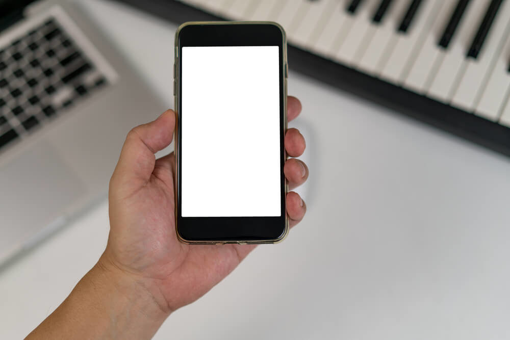 blank smartphone screen with a computer keyboard and a piano behind it